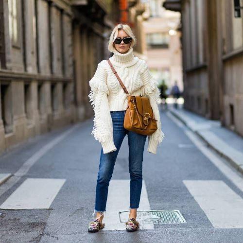 En dame står midt i gata iført tøfler, solbriller og genser med altfor lange ermer.